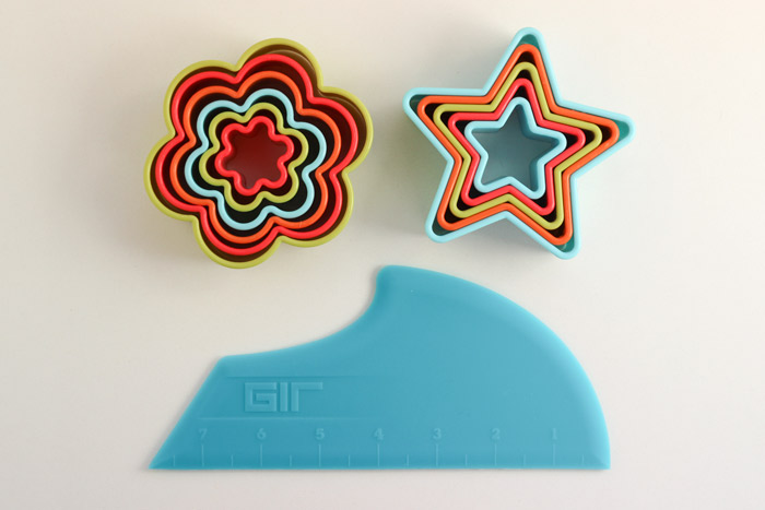 Clockwise from top:  flower cookie cutters ,  star cookie cutters , and  scraper .