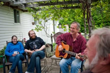 Heidi Tomes, Kieran Jedermann and Doug Dingledein (r) watch Dave Joyce strumm and sing