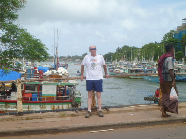 He wanted a photo in front of the harbor, but I wanted to wait until this other man was in the shot to capture the huge contrast between the Eastern and Western fashion.