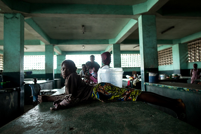 Hana, who sells donuts, lays across a counter once filled with meat products for sale in Monrovia, Liberia, on August 18, 2014. Waterside Market is typically a bustling commerce center in downtown Monrovia. Now, with fears of Ebola, vendors are struggling to sell their goods. The Liberian Government is threatening to close down the market which sits next to the largest township, West Point, where members of the community broke into an Ebola isolation unit on August 16. Because of concern that Ebola is spread through contaminated bush meat, stalls that used to be filled with meat are now empty.