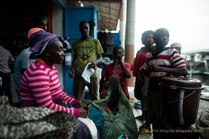Anne Benson, 49, sells used clothes in Waterside Market to support her nine children and five grandchildren in Monrovia on September 18, 2014. She lives with her husband and children in Sinkor. Since the Ebola outbreak her sales have plummeted. She used to sell the equivalent of $23 to $35 per day. Now she's lucky if she sells $6 worth. She says only people in town are buying. People are not traveling to the market anymore because of the costs of transportation and the fear of taxis, which are often carrying Ebola patients to Ebola Treatment Units. When she travels to work in a taxi, she protects herself from the other passengers in the car with a long sweater. She makes seven of her nine children stay at home all day to protect them from the Ebola virus and regularly uses hand sanitizer and their bucket of chlorine water at home.