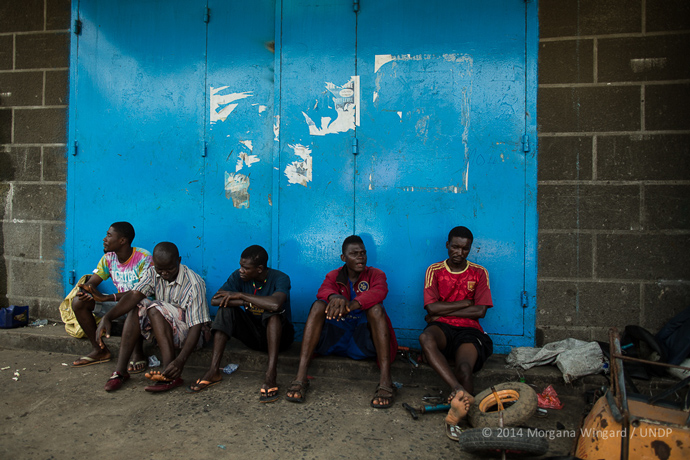 Vincent, 24 (center, in blue) and Junior, 20 (middle, in red), both residents of West Point, atownship that has been one of the hardest hit by the Ebola epidemic, used to drive motorcycles for a living — a form of local transport in Liberia used like taxis. After the government banned motorcycles in downtown Monrovia they had to stop. Now, because of Ebola, they can't find any work and are feeling disgruntled. They want a job, but no one is hiring so they wait on the side of the street at the entrance of West Point.