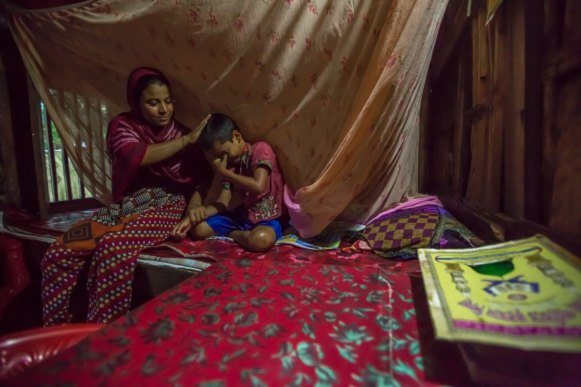 Ruma Begum, 28, a fish farmer in southern Bangladesh, helps her son, Bulbul, get ready for school.