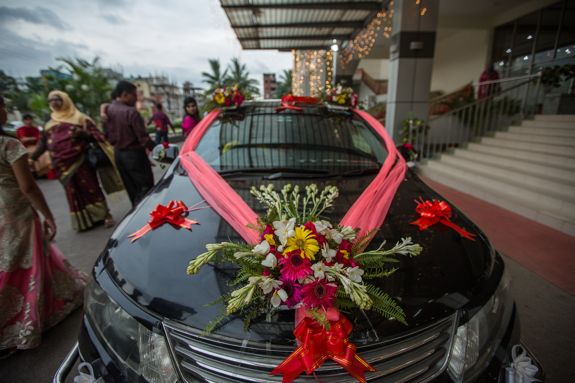 A bride and groom in Bangladesh ride off after their wedding ceremony with their car decorated with Gerbera flowers. Photo by Morgana Wingard
