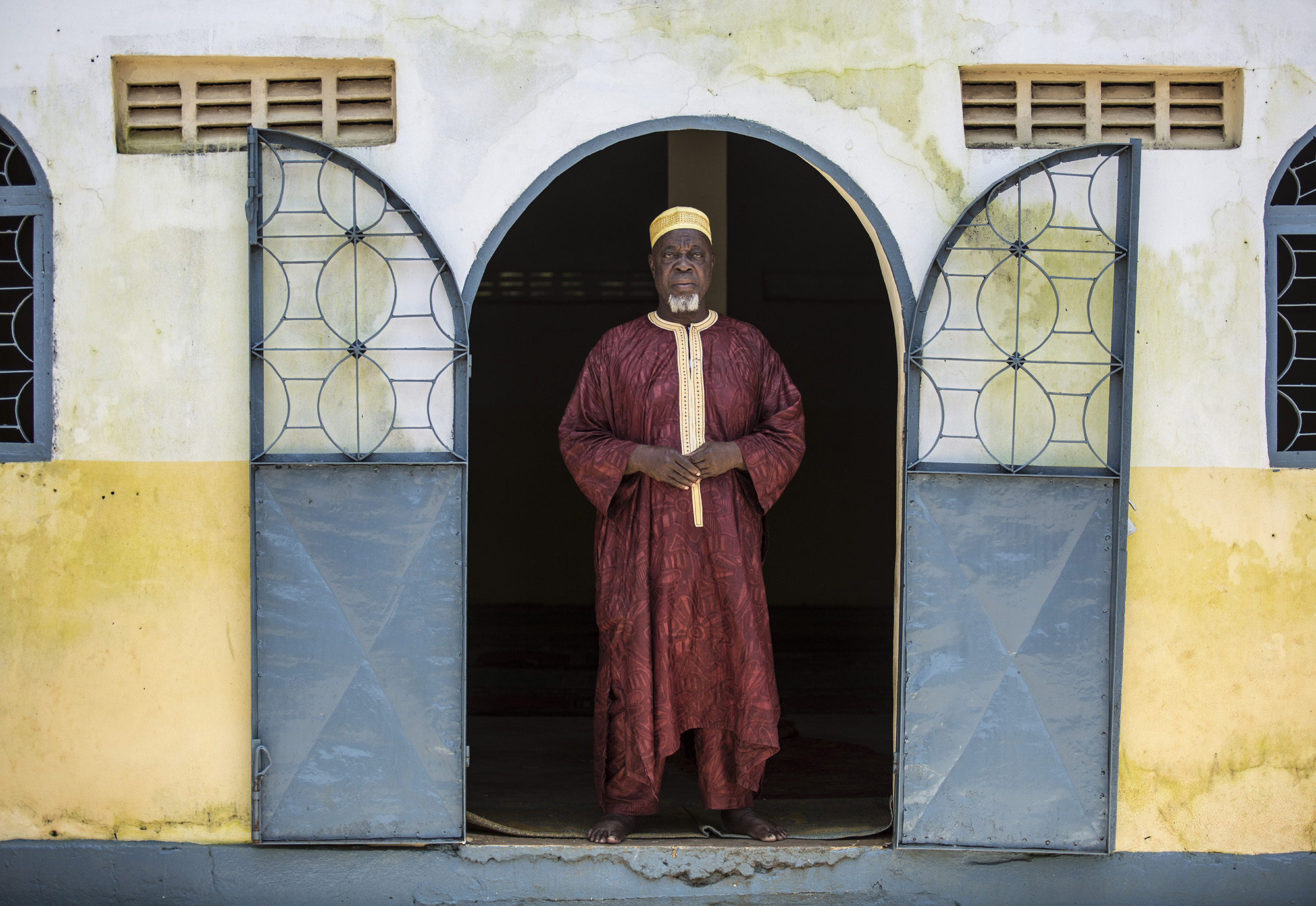 """CONAKRY, GUINEA: Imam Elhadj Cheikhouna Sylla has been an Imam for 40 years. Since the beginning of the Ebola outbreak he believed the rumors about the disease were true because there were so many stories about the diseases in the Koran. He was educated on Ebola by UNICEF and The Islamic Center. After this, he gave more than 20 speeches at the mosque to convince people that Ebola was real. He knew how important his role was since the beginning. He did his best in the community to promote safe burial. At his mosque, he was the one with the key. In the beginning, people wanted to give their loved ones who died of Ebola a proper funeral and burial at the mosque. He had to convince the community members that they could not do this unless they first contacted the Red Cross to prepare the body. Once completed, an authorization letter would be given to the family to proceed with a funeral. Once received, the Imam was able to allow the service at the mosque. He says, """" I knew I was impacting the community because they accepted to bring the paper delivered by the Red Cross and communities accepted the Red Cross to attend the burial. I witnessed two things. They took me and brought me to the Ebola Treatment Center (ETC) to see people who were sick with the disease. So this strengthened my belief with Ebola's existence. When there is a case in the community, I would sometime be called to go talk to the family members about taking the person to the ETC or about safe burial if they died. """"I was feeling sad for the families but am here to support them and to use the word of the holy Koran to help them. """" He said his advice to help use his own experiences to help convince community members that Ebola was real. Laughs...There are too many wishes that I have for Guinea. Ebola has affected the way communities have been living together and my hope is that there is more peace in the country. I wish for my country to get a good leader. Photo by Sarah Grile"""