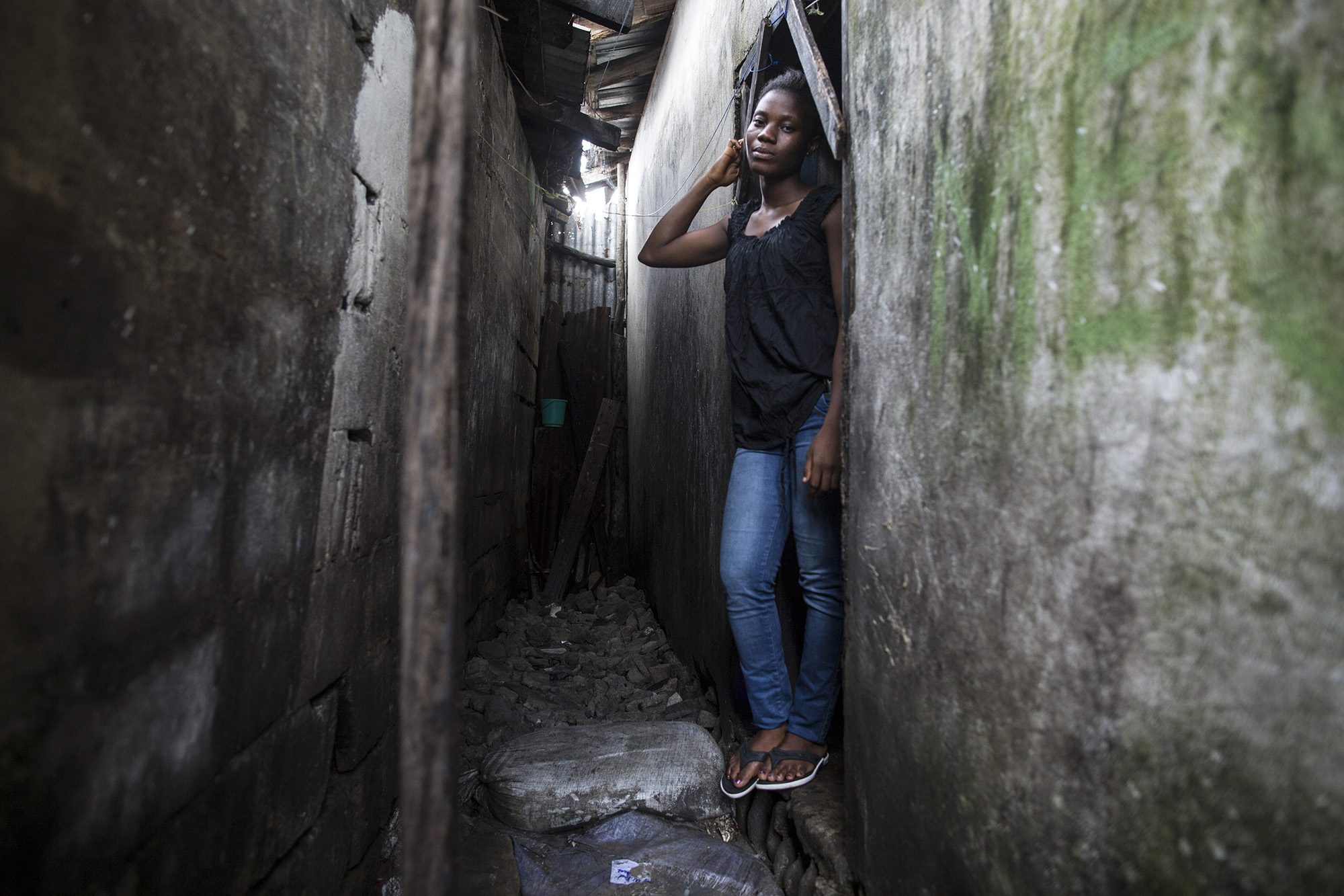 """MONROVIA, LIBERIA: Jessica Meufville,17, is a student in 10th grade in West Point — a slum in Monrovia's capital, Monrovia. Jessica was staying with her parents in West Point when Ebola came into the country. """"Sometimes I was really scared because of the information being spread around about Ebola. """"I was thought if I looked at someone with Ebola I would get it. If I came down with Ebola automatically all my family would get it."""" In August of 2014, West Point was quarantined after Ebola patients escaped from a holding center. She remembers finding out in the morning, since it occurred during the nighttime. She said, """"It was shocking to everyone. The whole time, everything was confusing, even your close friends you could not see. No one was moving. Everyone was staying at home."""" She and other young girls from West Point were part of a program headed by UNICEF's Hawa Page. These girls decided to meet at the West Point Women's Center. Their first meeting was on a Saturday. She remembers about 25 people being present. This is when they formed the group Adolescents Leading an Intense Fight Against Ebola or A-LIFE. She learned that Ebola was quite different then what was being spread around. We wanted to help save the lives of her fellow residents. """"We wanted to go door to door and tell people to follow preventative measures."""" They did training and were given protective wear. """"It was challenging. A lot of people never accepted the message. It used to make me feel bad. Our supervisor always used to encourage us. It was that motivation that kept me moving on to talk with people for more lives to be saved."""" They ended up doing the awareness for 6 months. Now, Jessica is back in school and hopes to become a journalist to """"help speak for the speechless."""" Photo by Sarah Grile"""