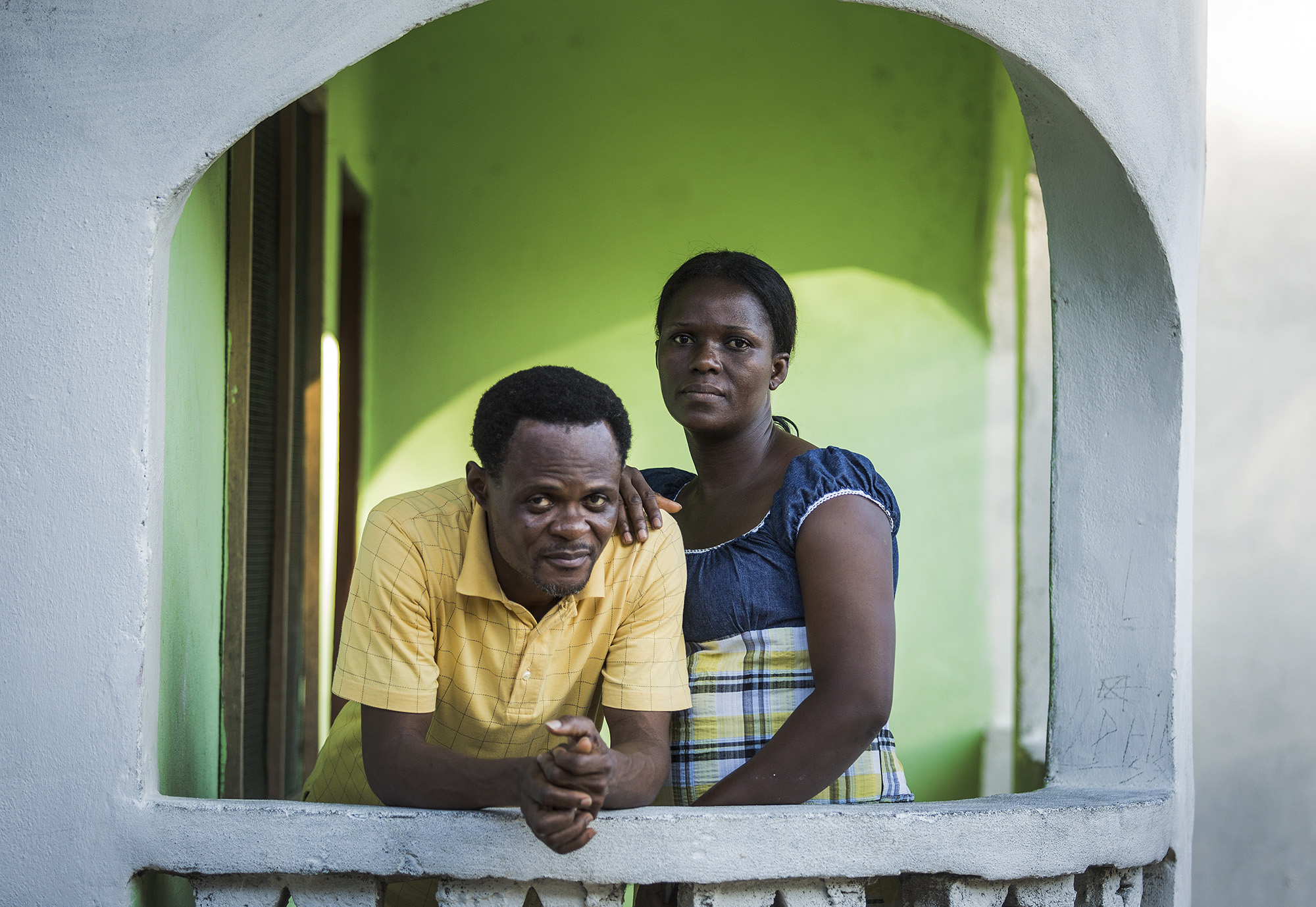 """NEW GEORGIA ESTATE, LIBERIA:Pastor John Prosper Ghartay Sr. with wife, Ophelia. """"I think it was the first Sunday in August. It was the time when Ebola was at its peak. The fear it brought. The segregation it brought among us in the community and as Liberians…there was no shaking of hands no touching. A member of our congregation died and her children were all sick. We took them to the ETU. I was afraid that I would get Ebola and infect a member of my family. I thank God, that by his grace we were able to get through the crisis and we're still alive. I would say Ebola made the community stronger because when it started everyone was afraid, everyone was staying home. We were not interacting, we were not touching. But when the Ebola kept increasing, the community would still come to the church every day, sharing information, giving Ebola updates, telling people how to handle anyone who is sick. By the grace of God we were able to fight as a community."""" Photo by Sarah Grile"""