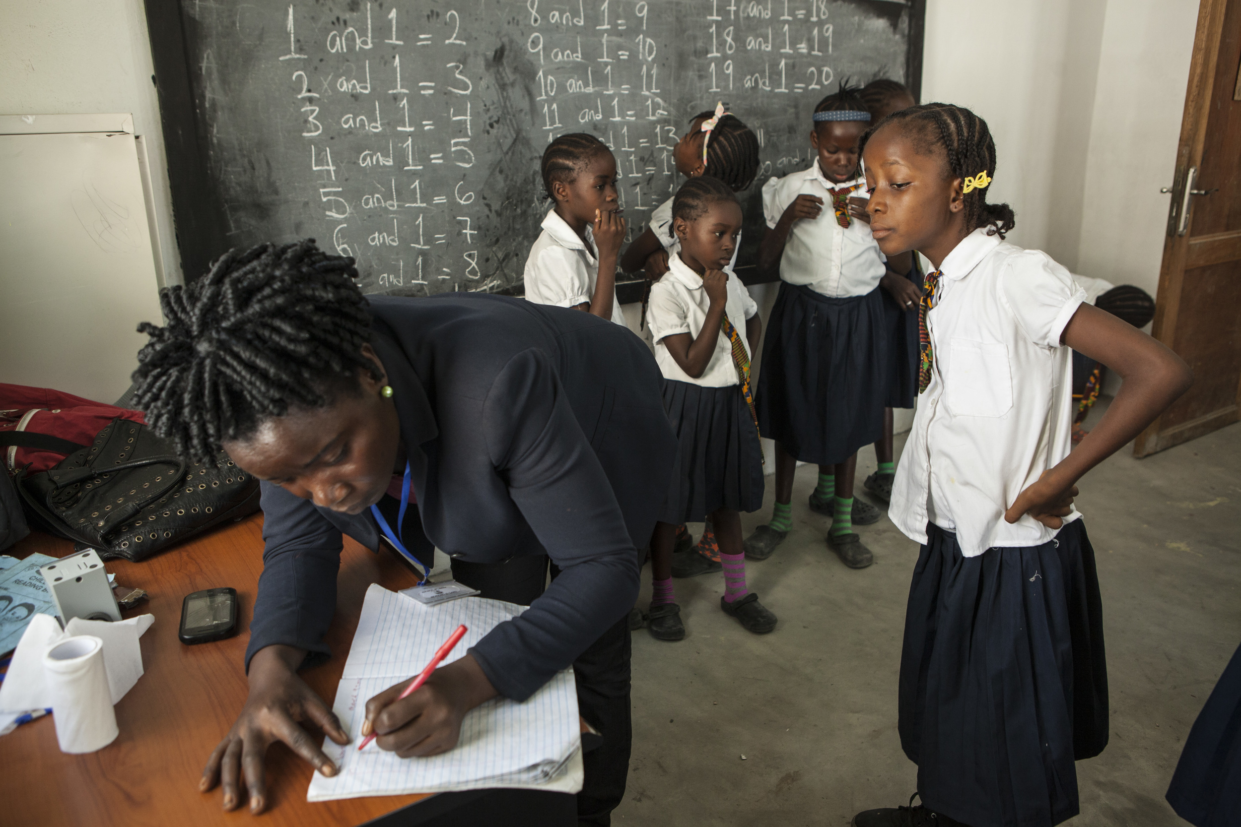 MONROVIA, LIBERIA - March 10, 2015: Mercy Kennedy, 9, is seen at the More Than Me Academy and in the school vehicle that takes her home. This is Mercy's first year attending school.