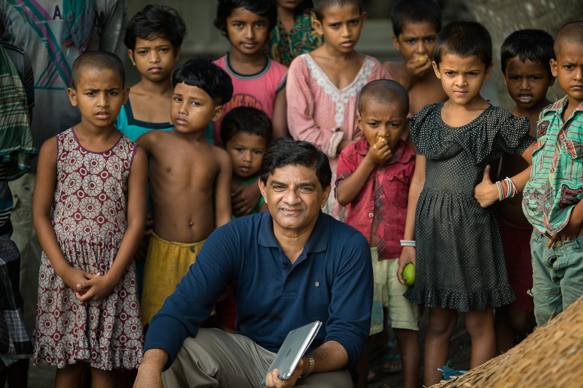 """UTTAR BORO MAGRA, BAKAL, AGAILIHARA, BARISAL, BANGLADESH: May 10, 2016 -  Taroni Kanta Shikari (means """"hunter"""" in Bangla), 45,  is a small farmer owning 3.65 acres of land. He lives with his wife, Baby, his mother, one son (Taposh) who reads in class 7 and one daughter Trishna (means """"thirst"""" in Bangla) who is in paramedic school. He has a brother who works in Dhaka. He completed his study up to grade 7. He could not continue due to the economic condition of his family. Taroni had to take responsibility for the family expenses. He started rice farming at a very young age. He married to Baby. They have  1 son and 1 daughter. At one stage he went to abroad to earn higher income and borrowed 200,000 Taka from his fellow farmers. But, he could not succeed in getting a good job abroad and returned back home to restart his rice farming. They used to live in a kutcha tin shed house.  He used to cultivate only Boro rice in his 3.65 acres of land.  He  did not follow any good rice farming practices such as line sowing, using integrated pest management (IPM) methods, good quality seed and balanced doses of fertilizers etc. He met the Feed the Future Accelerating agriculture Productivity Improvement (AAPI) Activity  staff and the field official of Department of Agricultural Extension (DAE) and got to know about good agricultural practices including use of urea deep placement (UDP) technology. He first received training from USAID AAPI Activity in 2010 and later also attended a motivational field visit. After receiving training he began using UDP technology and other improved practices in rice farming and vegetable crops for last 5 years. On an average he received an incremental production of about 0.4  metric tons (882 pounds) of Boro rice every year. His income increased every year due to improved productivity of rice crop and also other vegetable crops as he applied improved rice  farm management practices.  He used the additional income to repay what was left of his"""