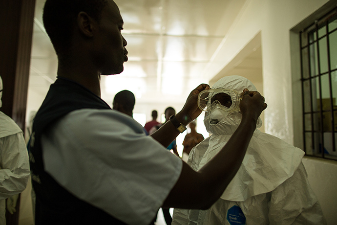 Health care workers put on personal protective equipment before going into the hot zone at Island Clinic, in Monrovia, Liberia on Sept. 22, 2014. The 100-bed clinic opened on Sept. 21, and within one day it is already at capacity after approximately 100 Ebola patients were moved from the nearby Redemption Hospital and ambulances brought other Ebola-stricken patients from the community. There are still more patients on the way. The facility was set up by the World Health Organization and Liberia's Ministry of Health in response to the surge of patients needing an Ebola Treatment Unit. USAID has provided two generators and other supplies the facility.