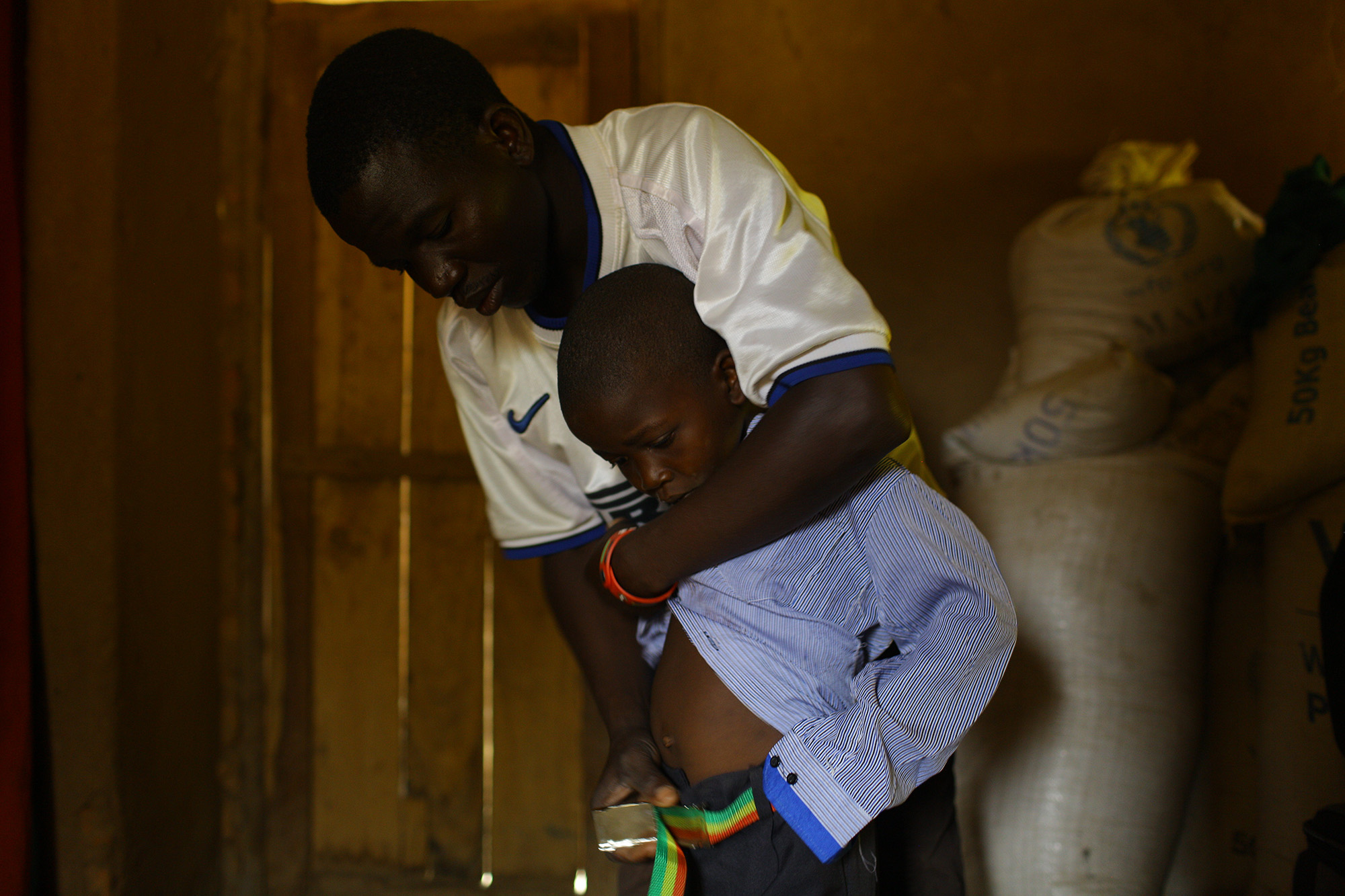 Wilfred Charles helps his son,Bright Wilfred, put on clothes.Photo by Morgana Wingard.