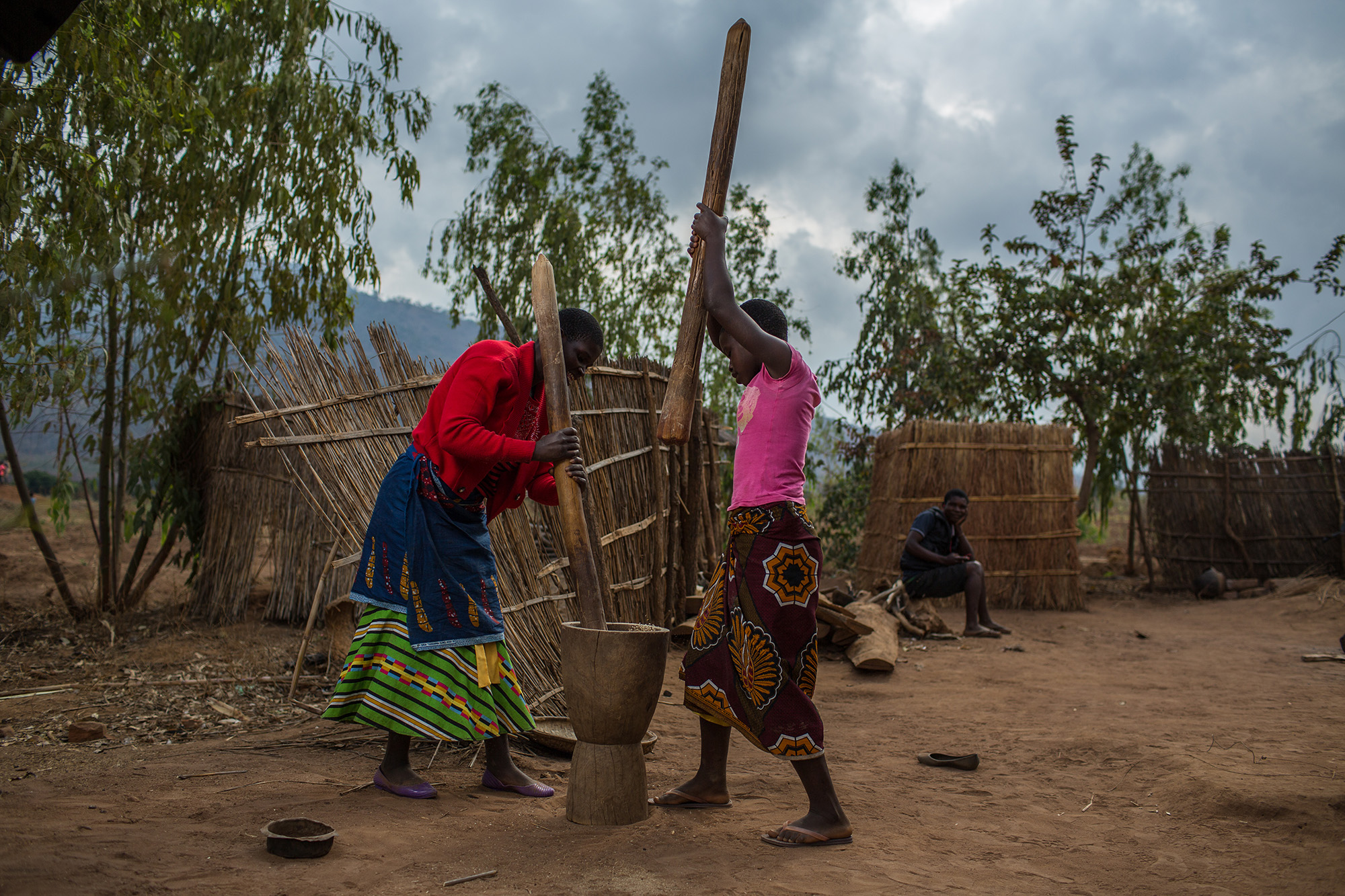 Wilfred's wife, Magrate Nthawani, left, and daughter,Joyce Wilfred, prepare food outside their house.Photo by Morgana Wingard.