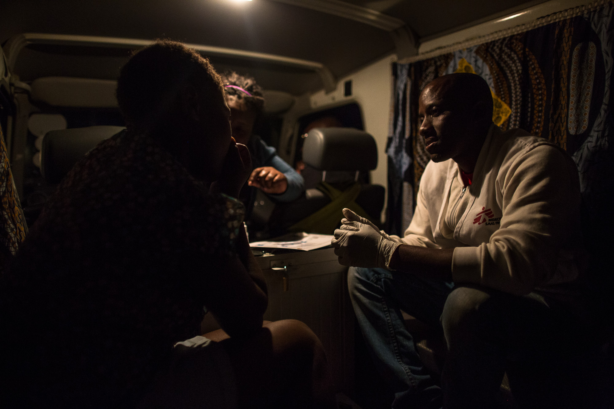 MSF peer educator, Constantino, tests a comercial sex worker for HIV, yellow fever and Syphilis while Patti, another MSF peer educator, counsels her inside of the MSF vehicle in her neighborhood. She was last tested in 2014, but this is the first time she's been tested by MSF. This time she tested negative for HIV and yellow fever, but positive for syhpillis.