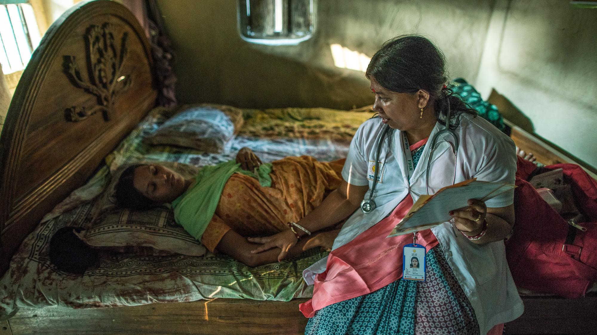 Shanta Das, a paramedic at Smiling Sun Clinic, consults a pregnant mother at her home.