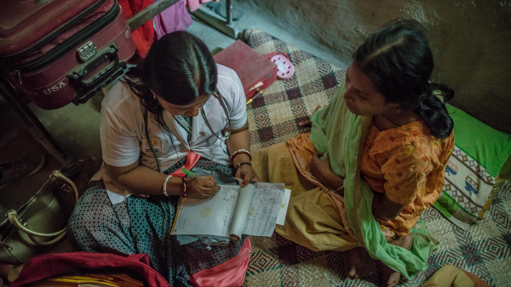 Shanta Das, a paramedic at Smiling Sun Clinic, consults a pregnant mother at her home