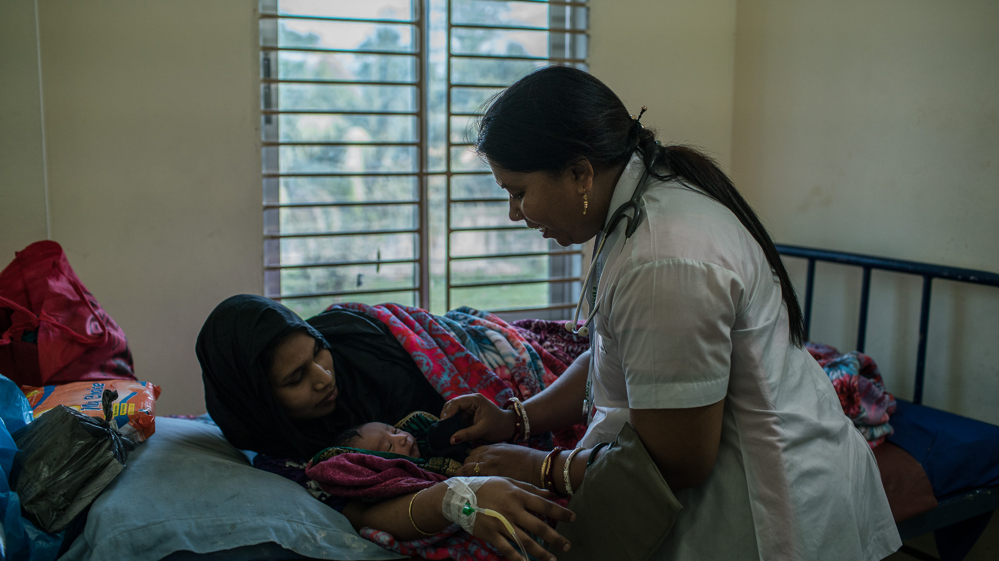 Shanta Das, a paramedic at Smiling Sun Clinic, consults with patients.