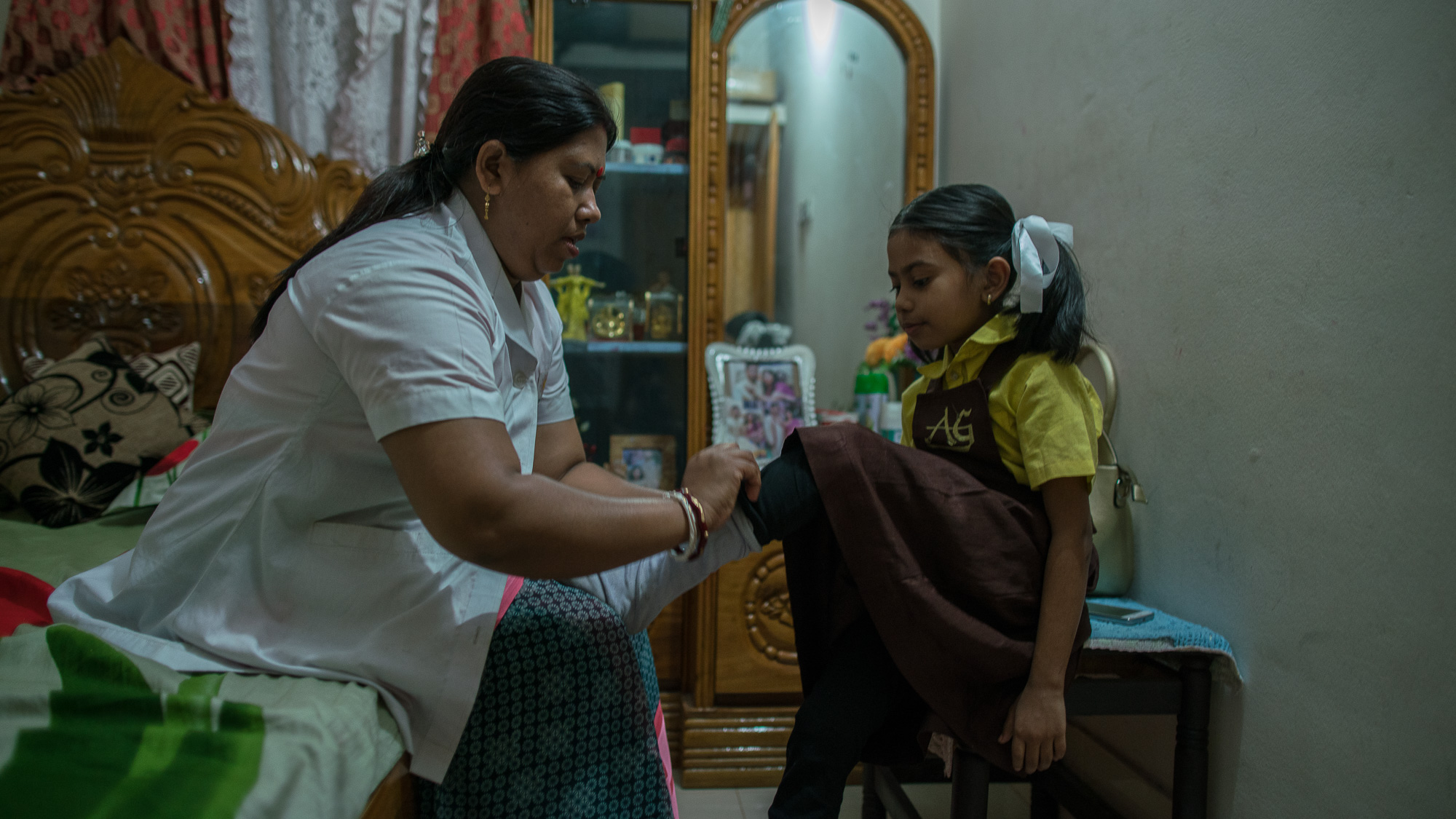 Shanta Das, a paramedic at Smiling Sun Clinic, helps her daughter, Ankita, get ready for school in the morning.