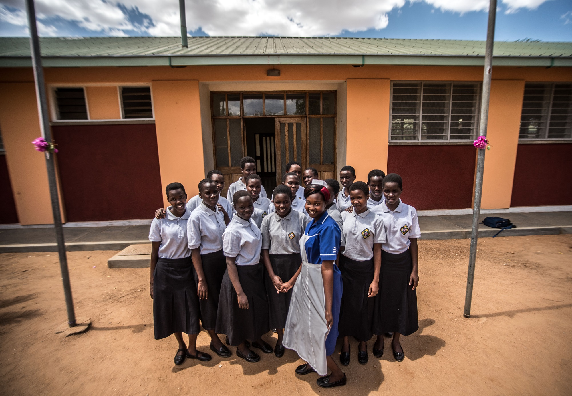 Students on Intrahealth-funded scholarships at the Matany School of Nursing and Midwifery in Karamoja, Uganda, pose for a picture in front of the school building.