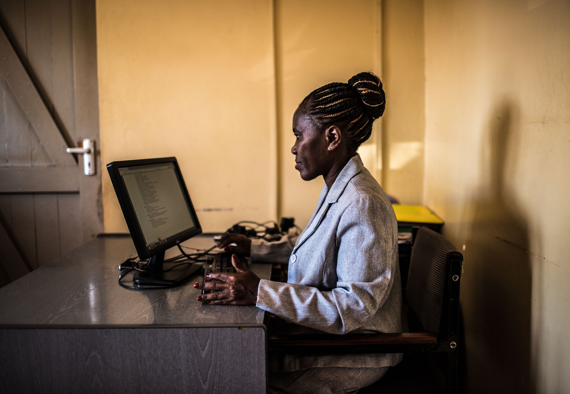 Justine Kaboole, regional focal person for Hris in Iganga, Uganda, uses the software on her comuter at the DHO's headquarters.