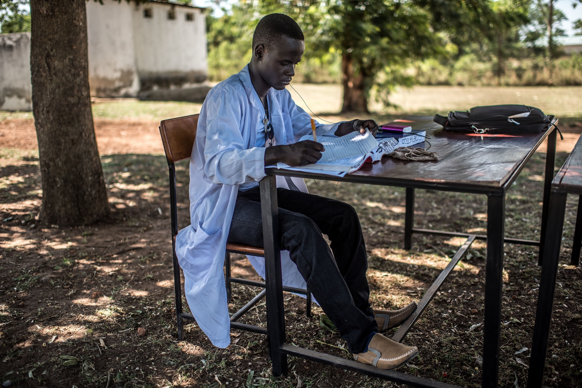 Students of the Soroti Pharmacy Schoolrelax and revise in the shade of a tree.