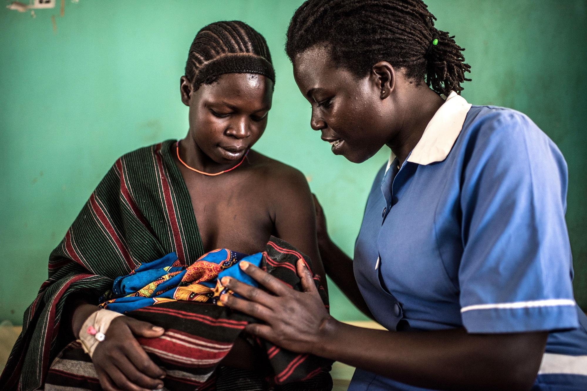 Munges Veronica, 24, holds her newborn baby, Teko, with Atim Jane, a 38 year old nursing officer at the Nadunget Health Center 3 in Karamoja, Uganda.