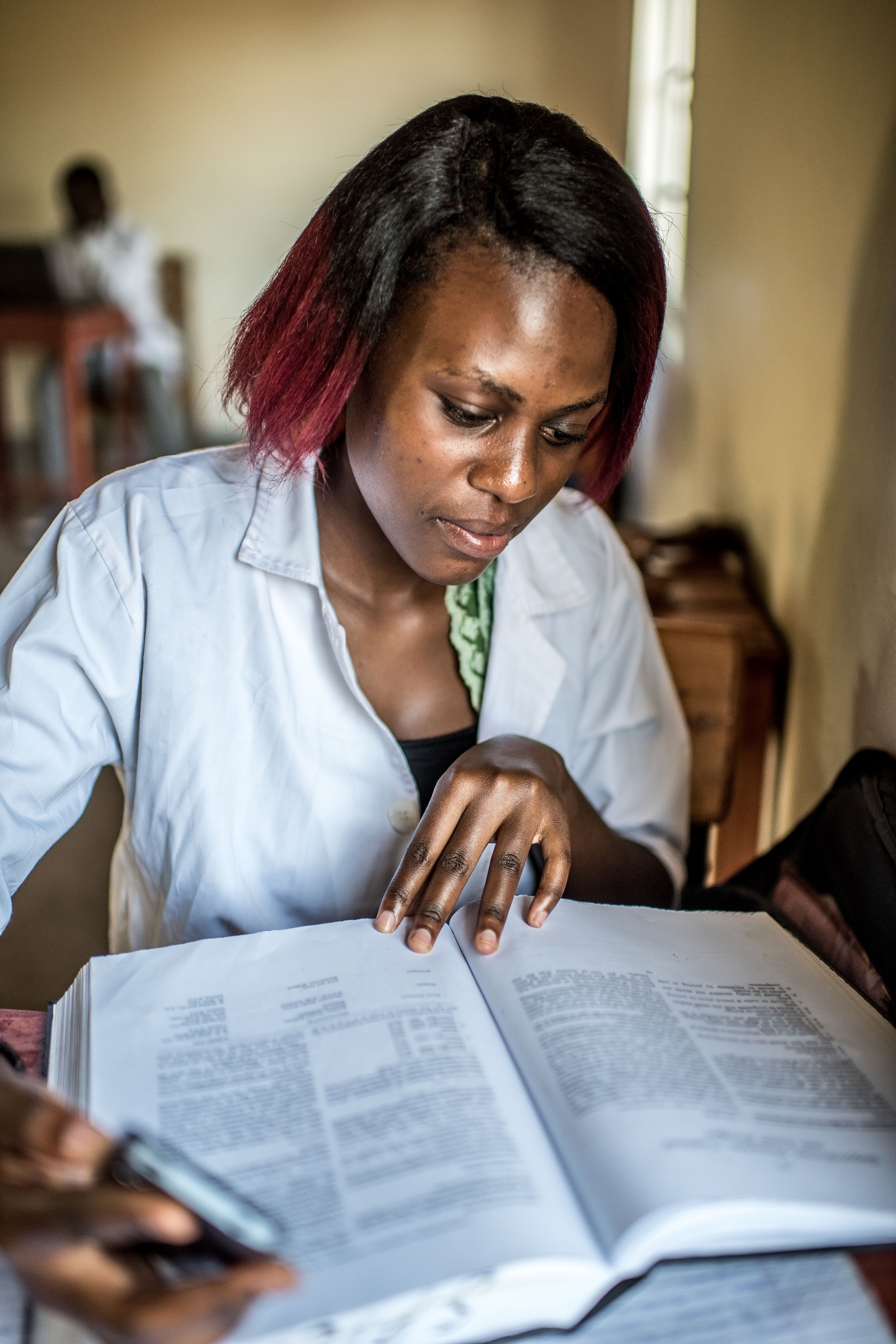 Helen Namuyaba, 22, a student at the Soroti Pharmacy School, takes notes during a class.