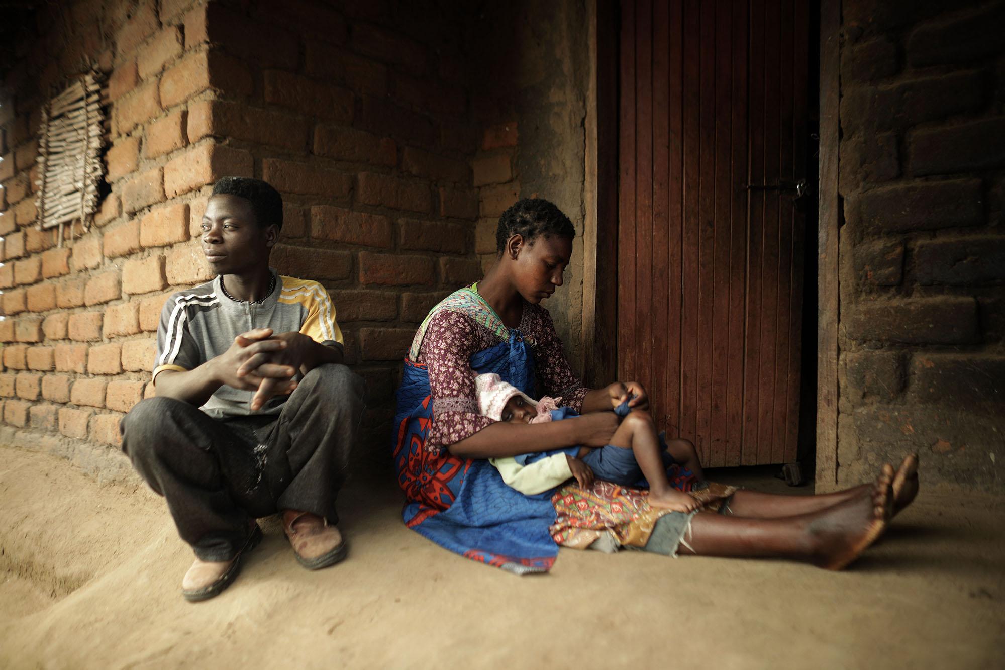 Mariam Chinguwo holds her daughter, Maness, while her husband, Hastings Sandikonda, looks on.
