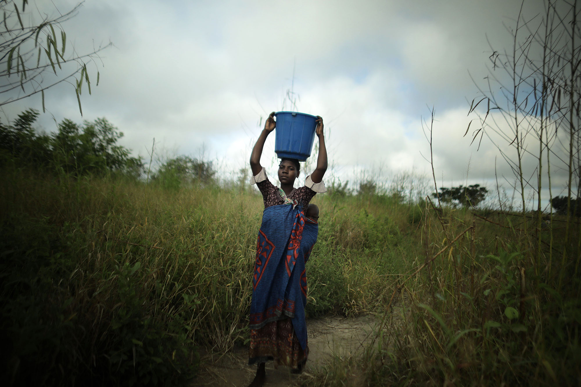 Mariam Chinguwo brings water back to her house. Photo by Josh Estey.