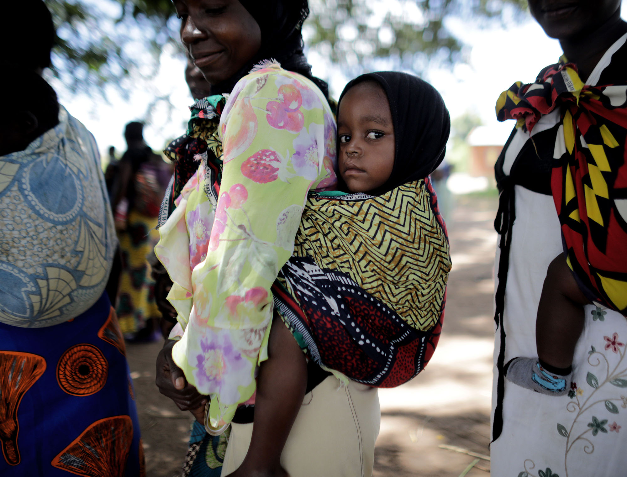 """Women began to gather under the shade of a large tree in TA Nsamala, with baby's on their backs. The program implemented by the government and supported by UNICEF is part of the """"improvement of nutritional and health situation for children under 5, women, internally displaced persons and refugees."""" Photo by Josh Estey."""