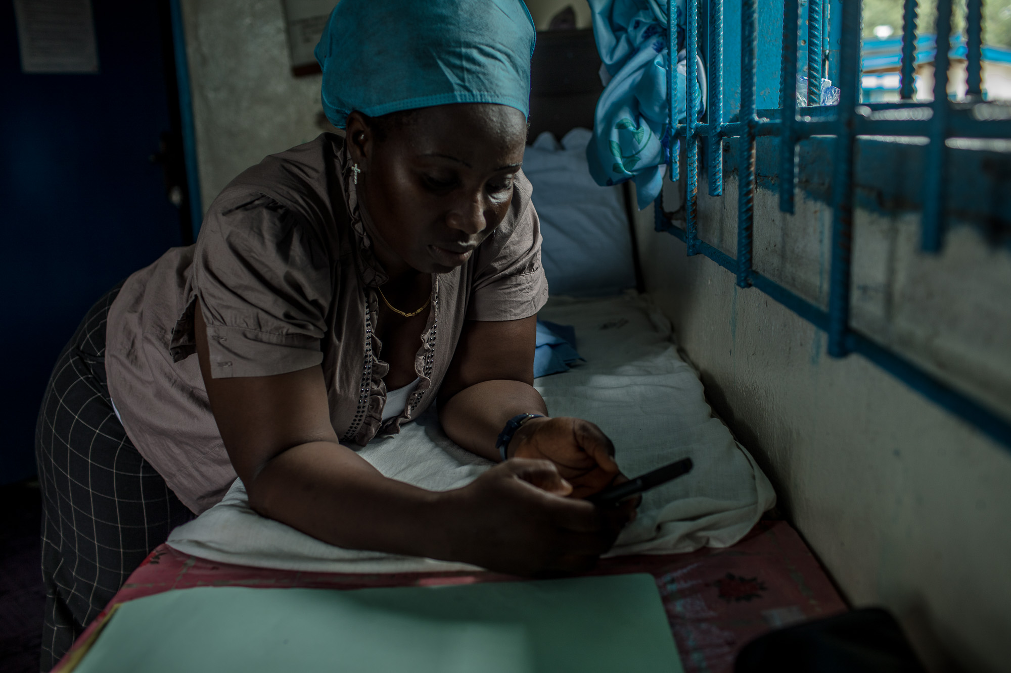 BREWERVILLE, LIBERIA: August 22, 2017 - Wislyne S. Yarh Sieh is a registered nurse at Kpallah Community Clinic in Browerville—just outside of Monrovia, Liberia. She was a healthcare worker during the Ebola outbreak in 2014-2015. During that time there was no centralized system for the Ministry of Health to communicate to all healthcare workers across the country at the same time. UNICEF and USAID teamed up to create a platform that utilized mobile phones to facilitate a two way communication system between healthcare workers and the centralized ministry. Now Wislyne receives text messages on her phone with vital information when there is a health emergency. She can also use her phone to send important information like the status of supply stocks in the clinic. Photo by Morgana Wingard