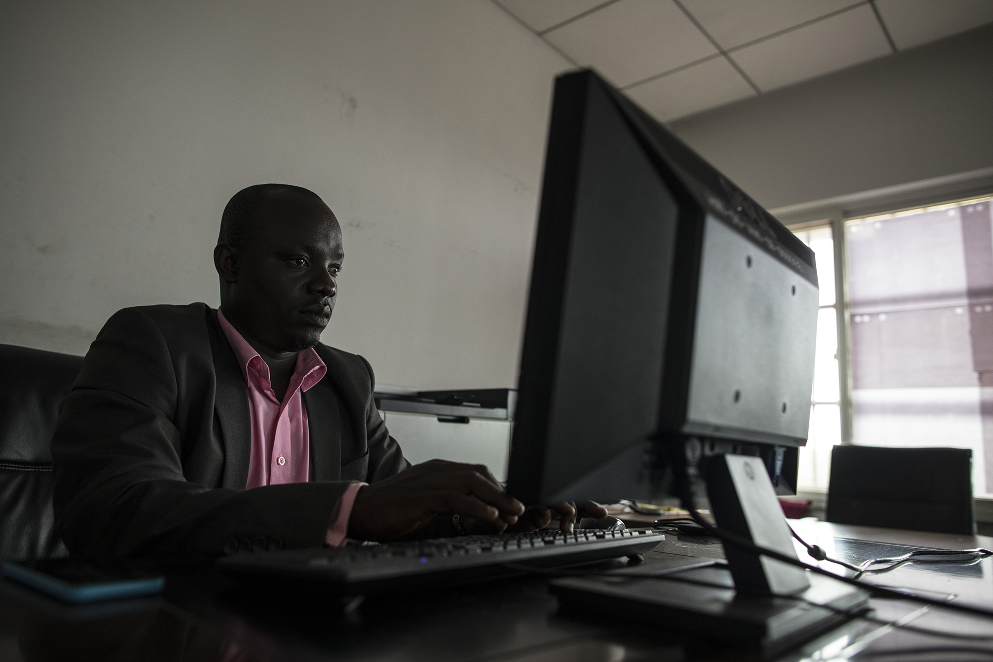 MONROVIA, LIBERIA: August 23, 2017 -  During the Ebola outbreak that started in 2014 there was no centralized system for the Ministry of Health to communicate to all healthcare workers across the country at the same time. UNICEF and USAID teamed up to create a platform that utilized mobile phones to facilitate a two way communication system between healthcare workers and the centralized ministry. Now healthcare workers receive text messages on their phones with vital information when there is a health emergency. They can also use their phones to send important information like the status of supply stocks in the clinic. Photo by Sarah Grile.