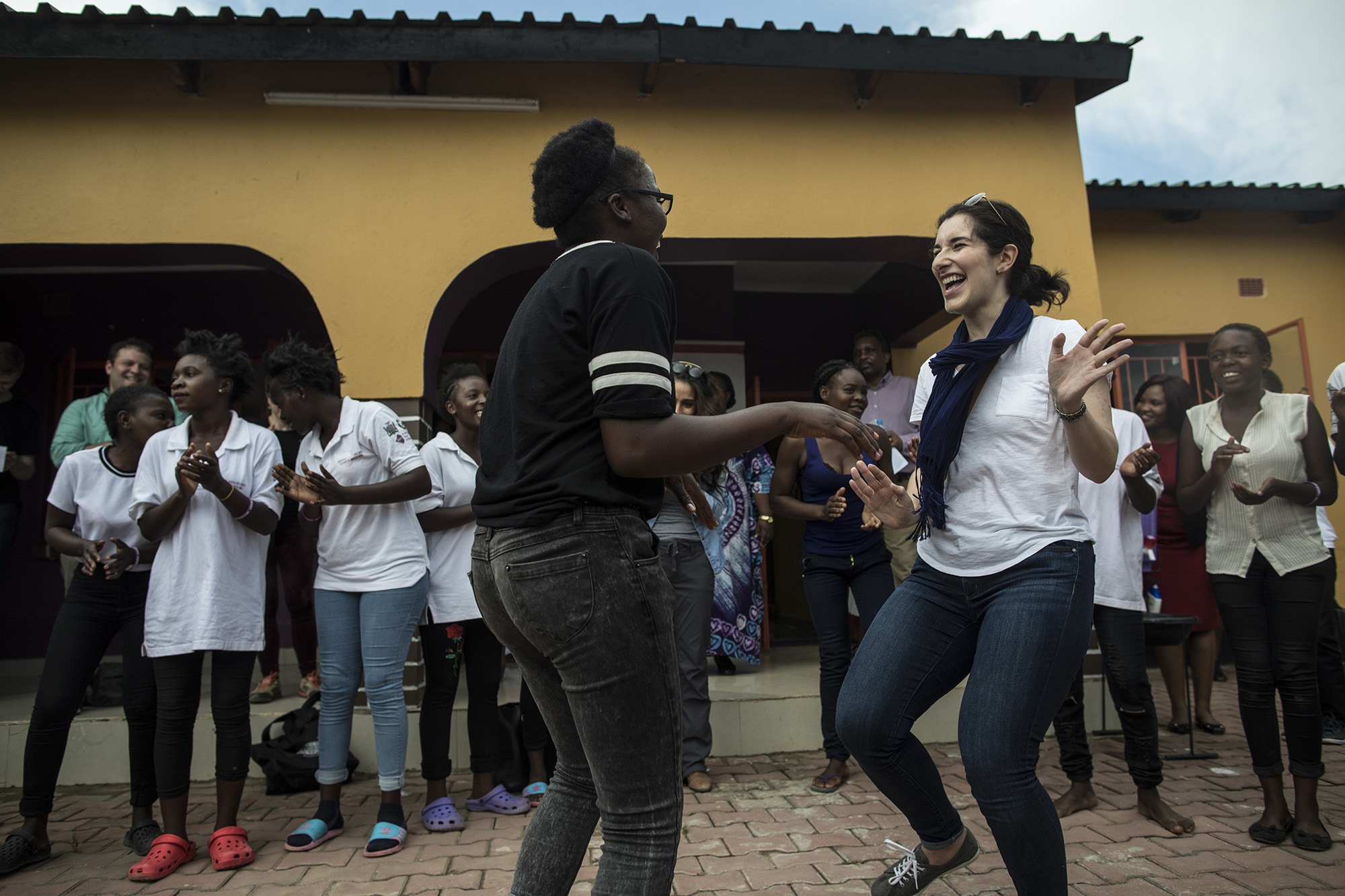 LUSAKA, ZAMBIA: Feb. 19, 2018 - The CARE Learning Tour to Zambia delegation visits a DREAMS Center in Lusaka, Zambia on Feb. 19, 2018 to learn more about how the center's services play an important role in the community for adolescent girls and young women. Here, Liz Leibowitz, top center, Foreign Affairs Legislative Assistant for Rep. Nita Lowey, dances with girls from the DREAMS program and other CARE Learning Tour to Zambia delegation members after touring the center's facility. Photo by Sarah Grile.