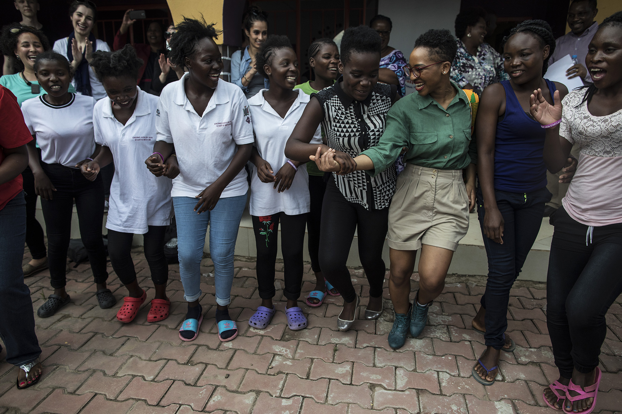 LUSAKA, ZAMBIA: Feb. 19, 2018 - Mia R. Keeys, third from right, Health Policy Advisor to Congresswoman Robin Kelly (D-IL), dances with girls from the DREAMS Center and other CARE Learning Tour to Zambia delegation members after touring the center's facility. Photo by Sarah Grile.