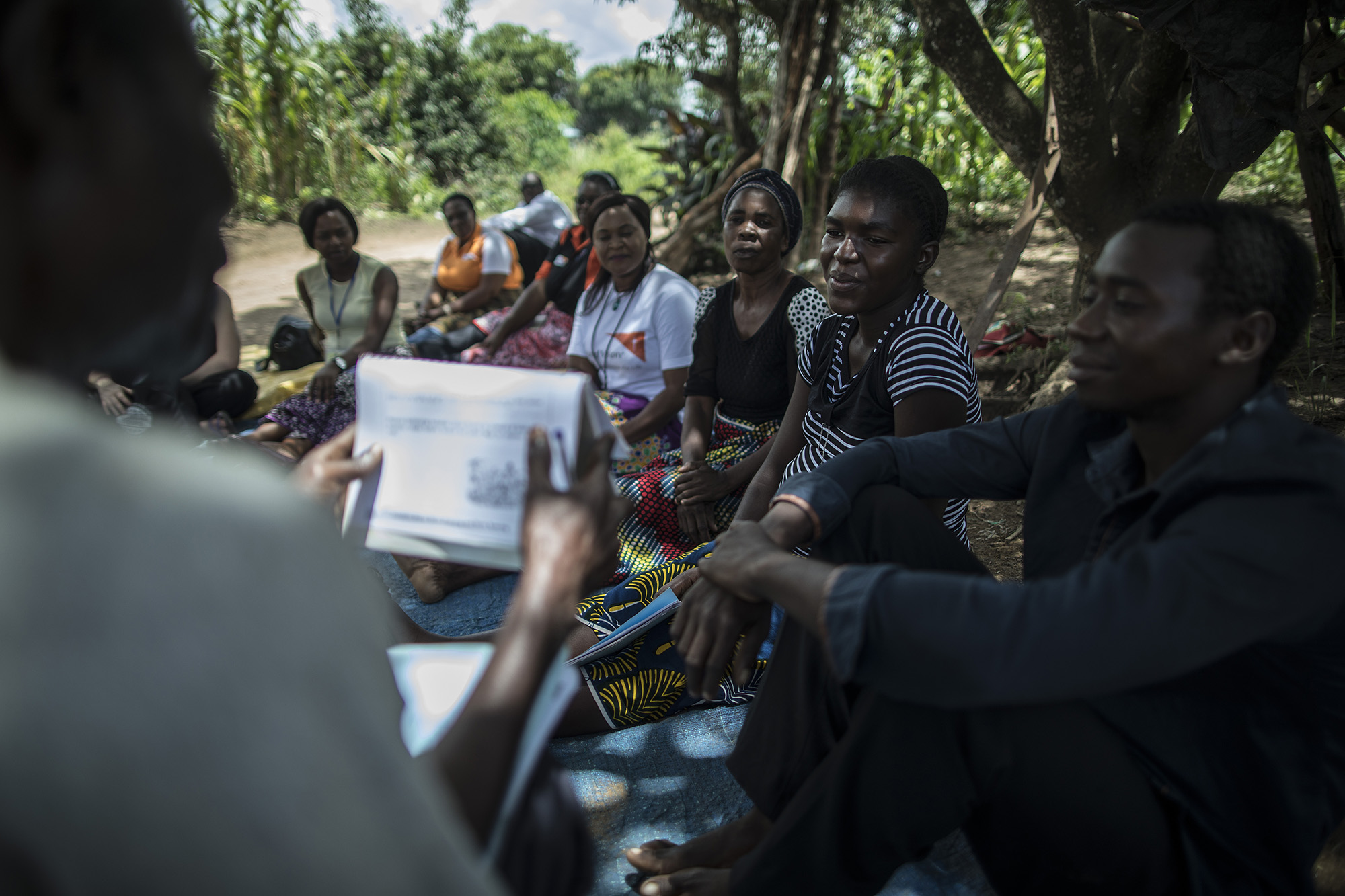 CHONGWE, ZAMBIA: Feb. 19, 2018 - Members of the CARE Learning Tour to Zambia delegation watch as Dennis Chulu, left, goes over a birth planning story with David Hachitamba, right, and his wife, Memory Hachitamba, second from right, during a SMAG home visit simulation near the Hachichamba's house in Chongwe. Photo by Sarah Grile.