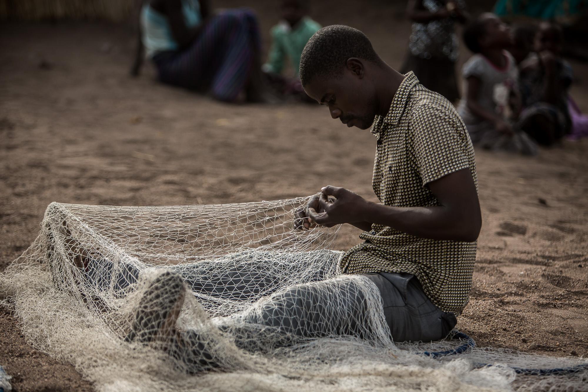 Jacob Rajah inspecting and repairing fishing nets