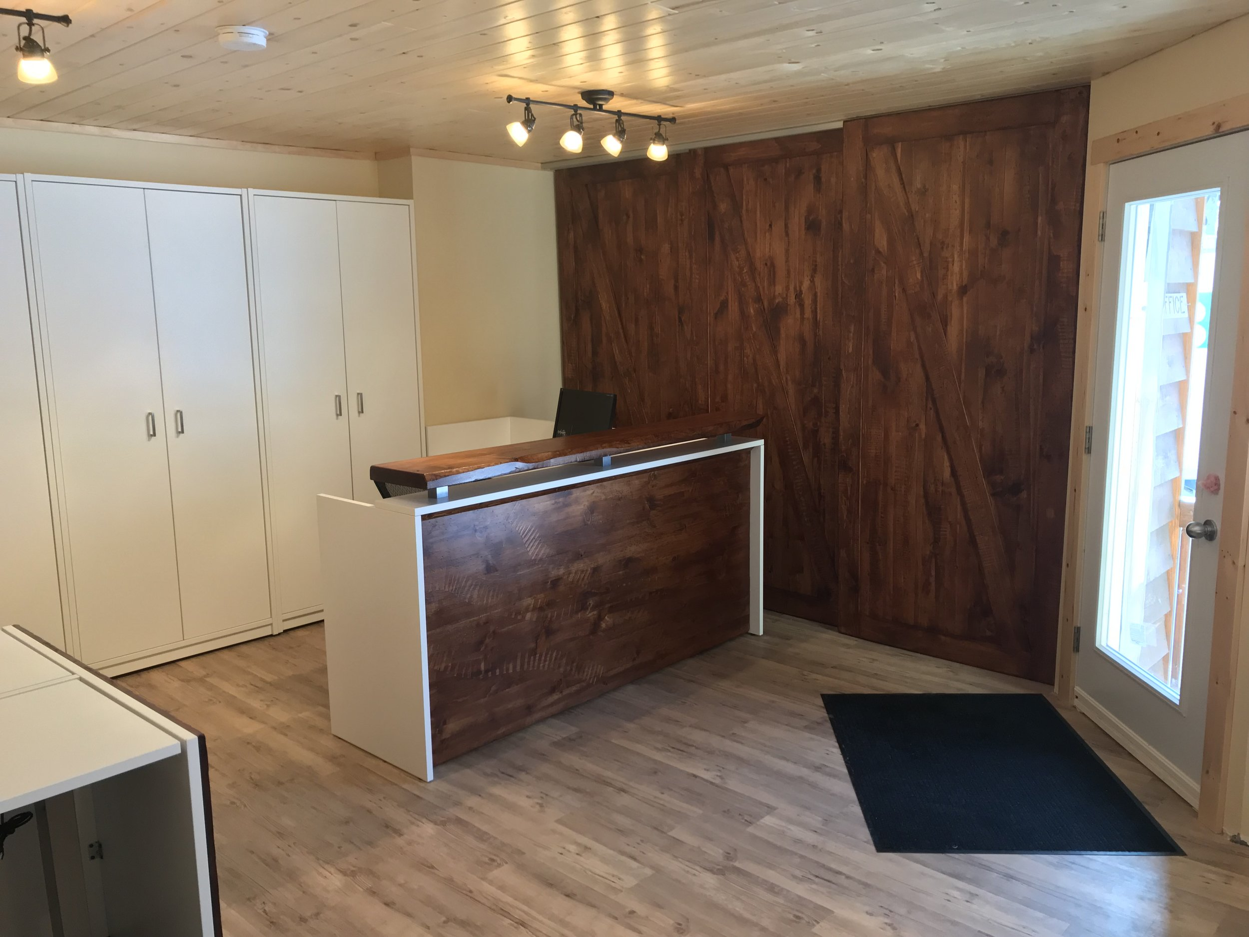 """Our new reception desk, with some great barn doors hiding the electrical panels we couldn't completely cover. The great thing about this desk (and the new front door) is that we can now see right down the camp road for those arriving at camp, so we don't have to """"wonder"""" who's arrived!"""
