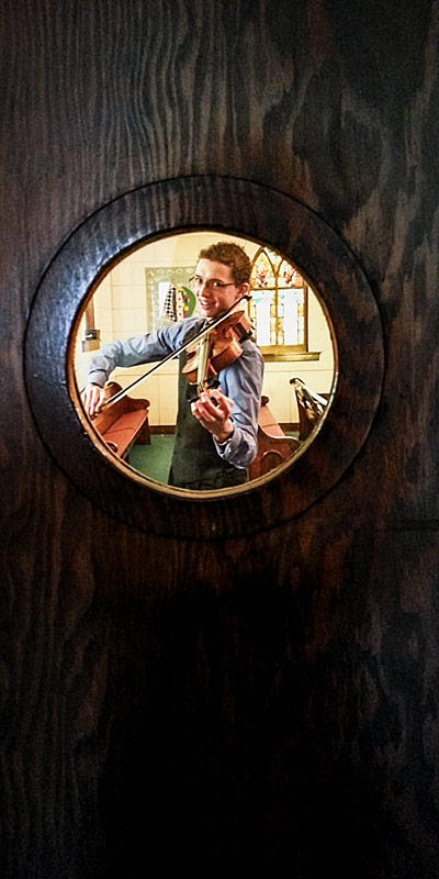Tuning da viola for da concert: a photo-worthy occupation when the photographer spots a neat window in the door just begging to have its picture taken.