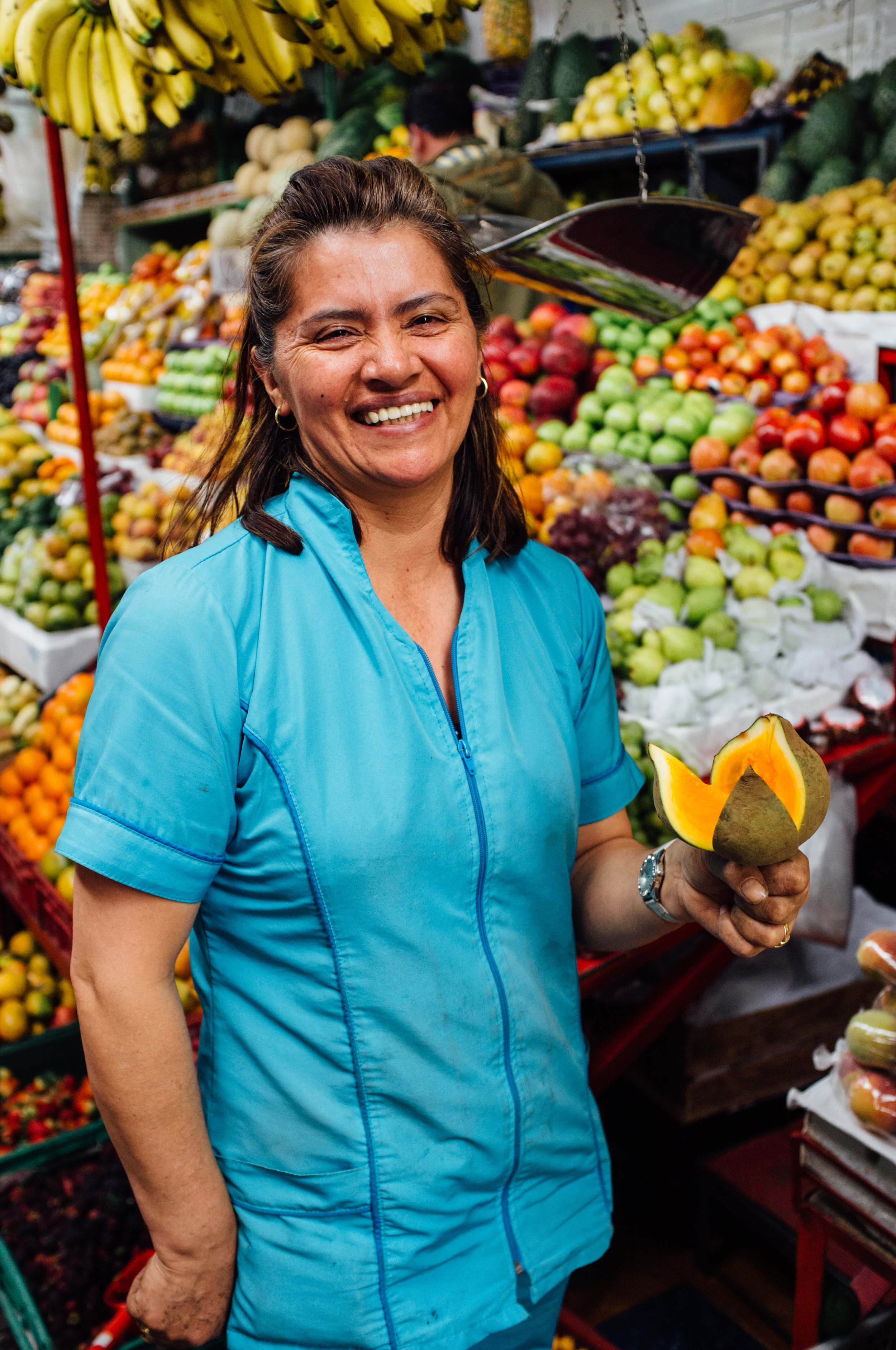 Chatica, a vendor at theMercado de Paloquemao, modeling a nísperofor us