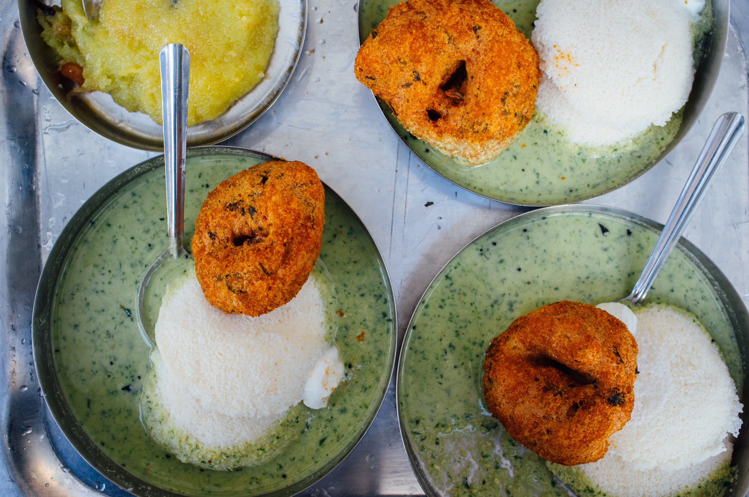 Idli  and  Vade  at Brahmin's in Bangalore. Note the dollop of homemade butter on every plate.