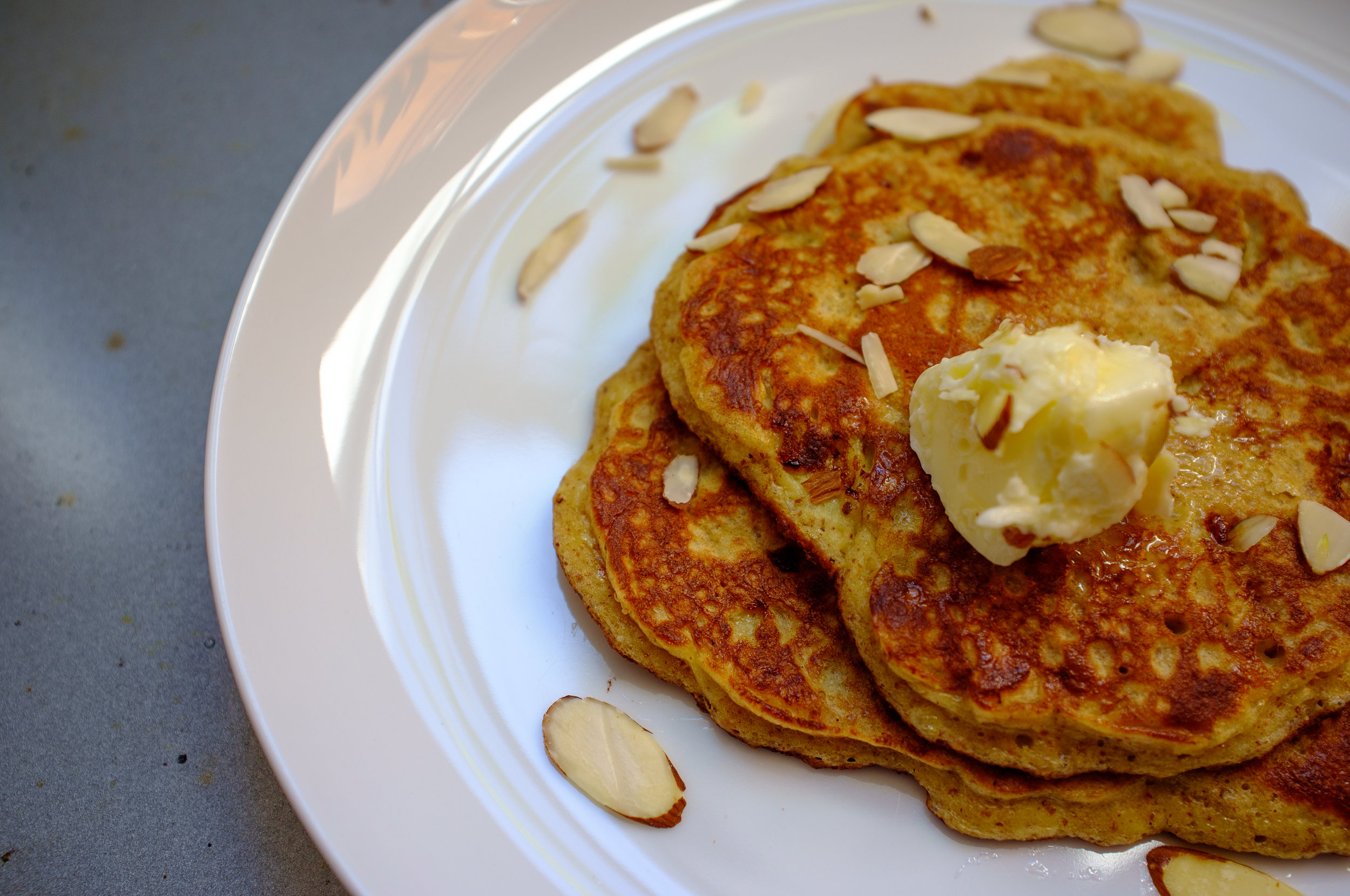 Paleo pancakes topped with butter and slivered almonds