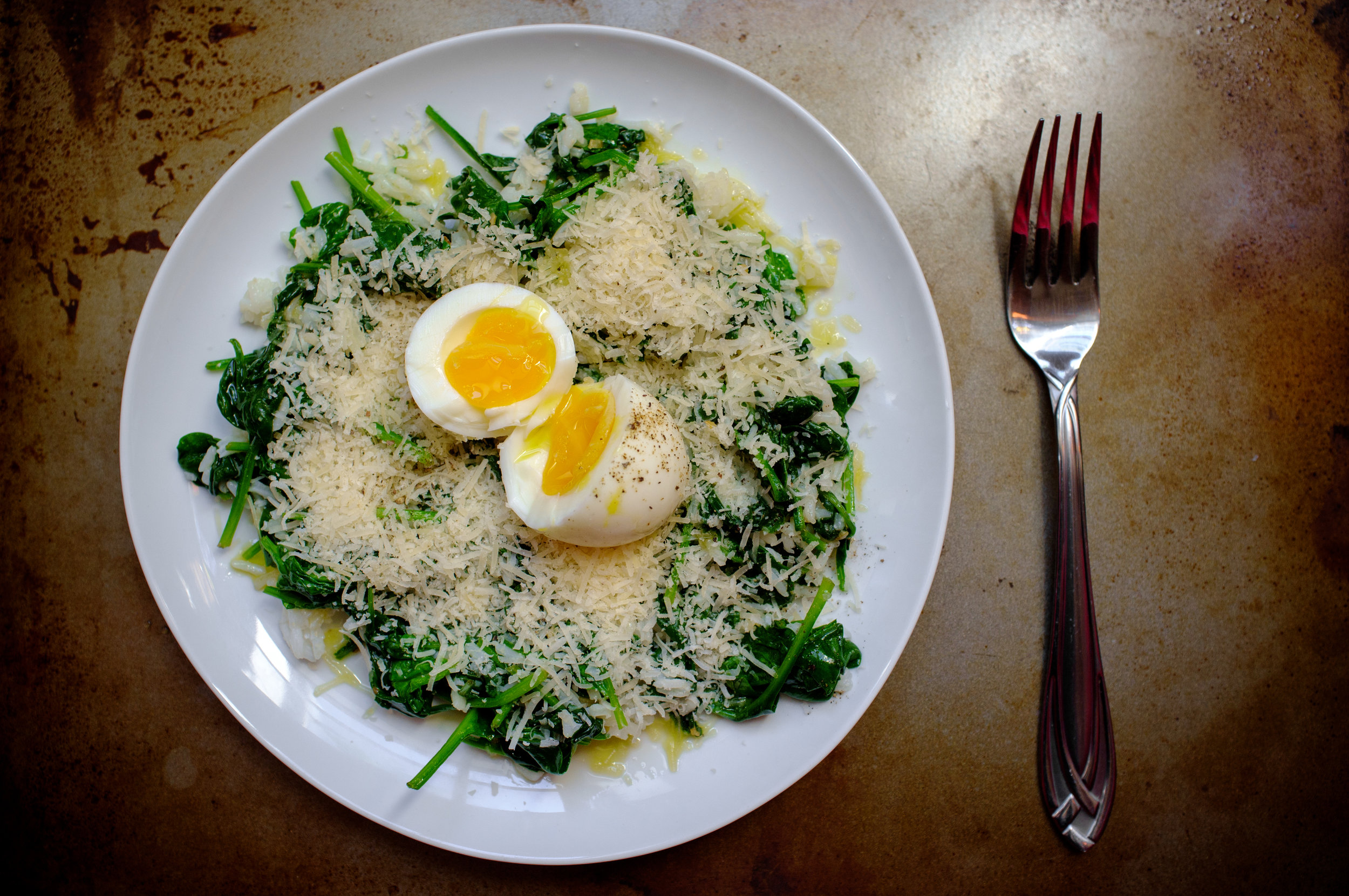Leftover rice, sautéed spinach and cheese topped with an egg