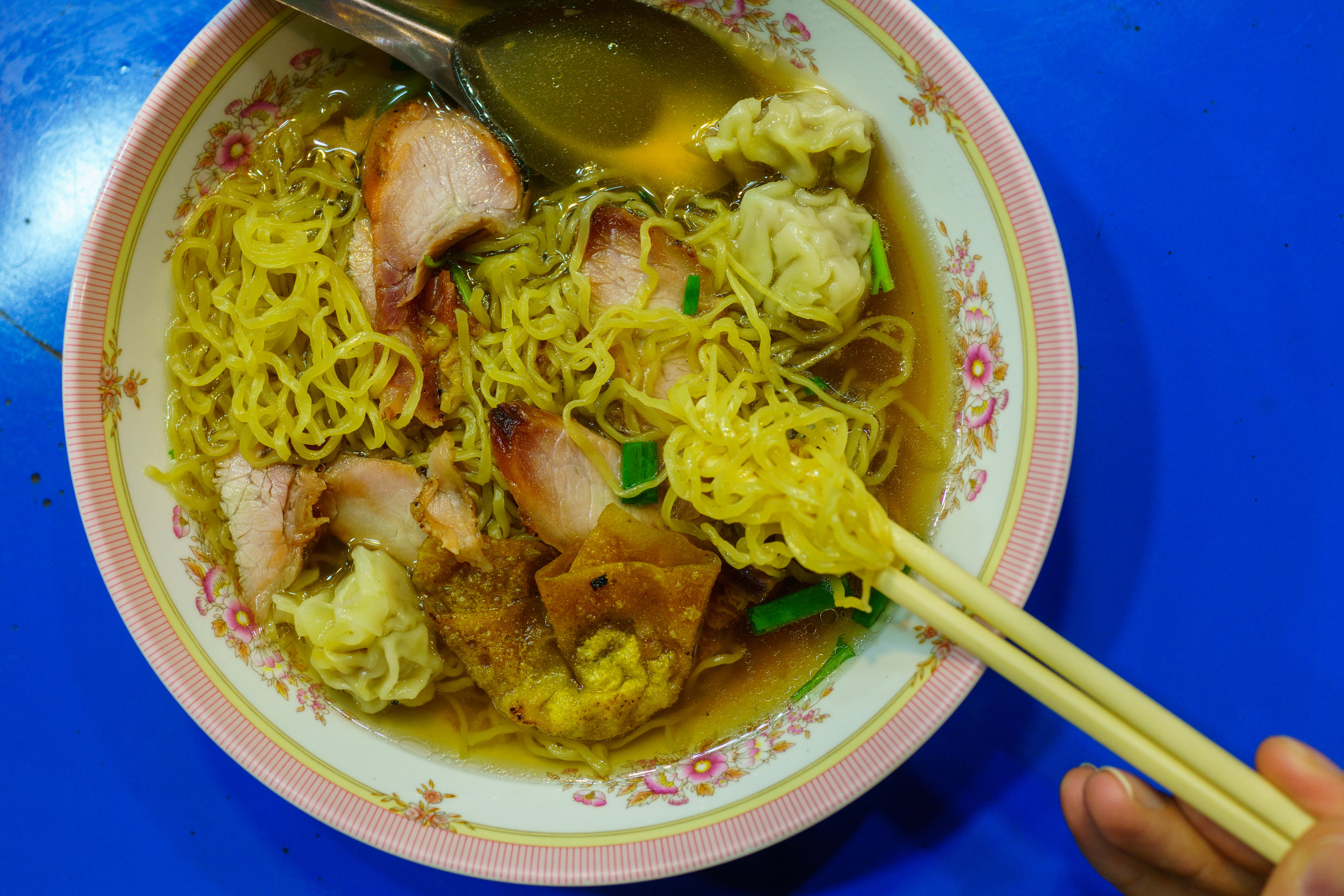 We stopped for hot bowls of noodle soup at a covered street food vendor on a rainy night; wonton noodle soup