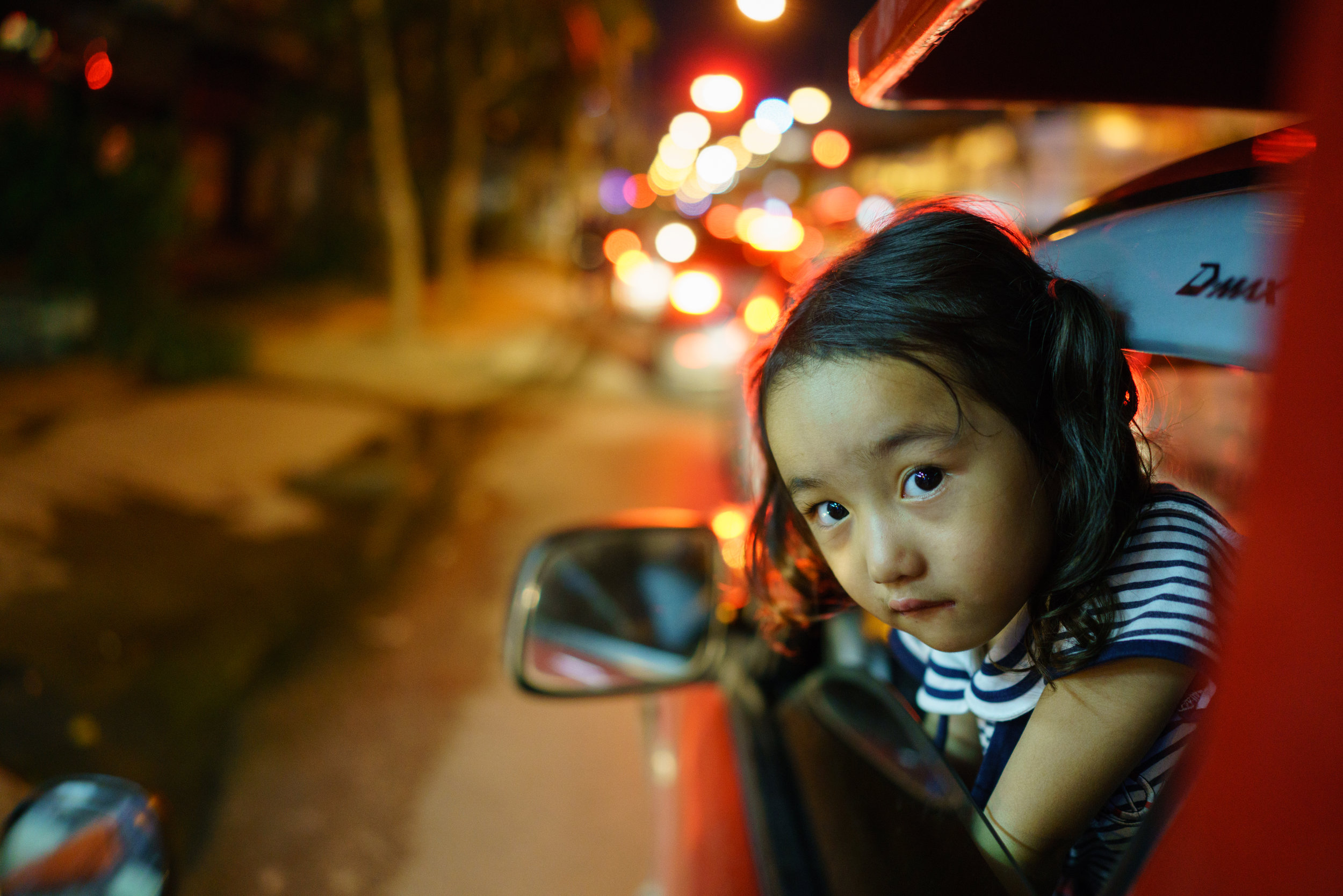 Often you'll find families of the  songthaew  driver sitting up front; here a young girl plays peekaboo with Prem from the front seat