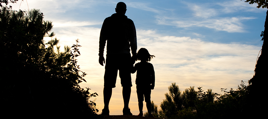 Silhouette of man and little girl