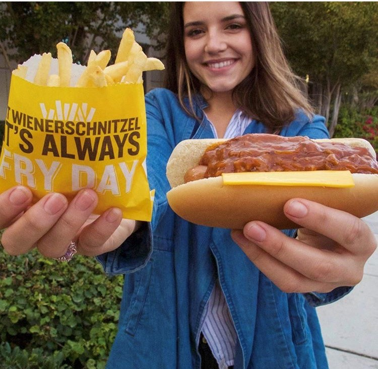 Account management intern holding Wienerschnitzel hotdog and fries