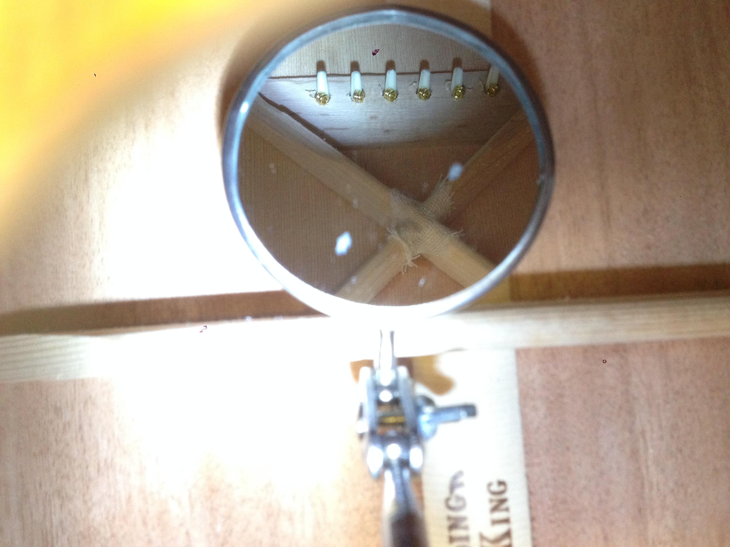 String Balls Against Bridge Pad Inside Guitar Body