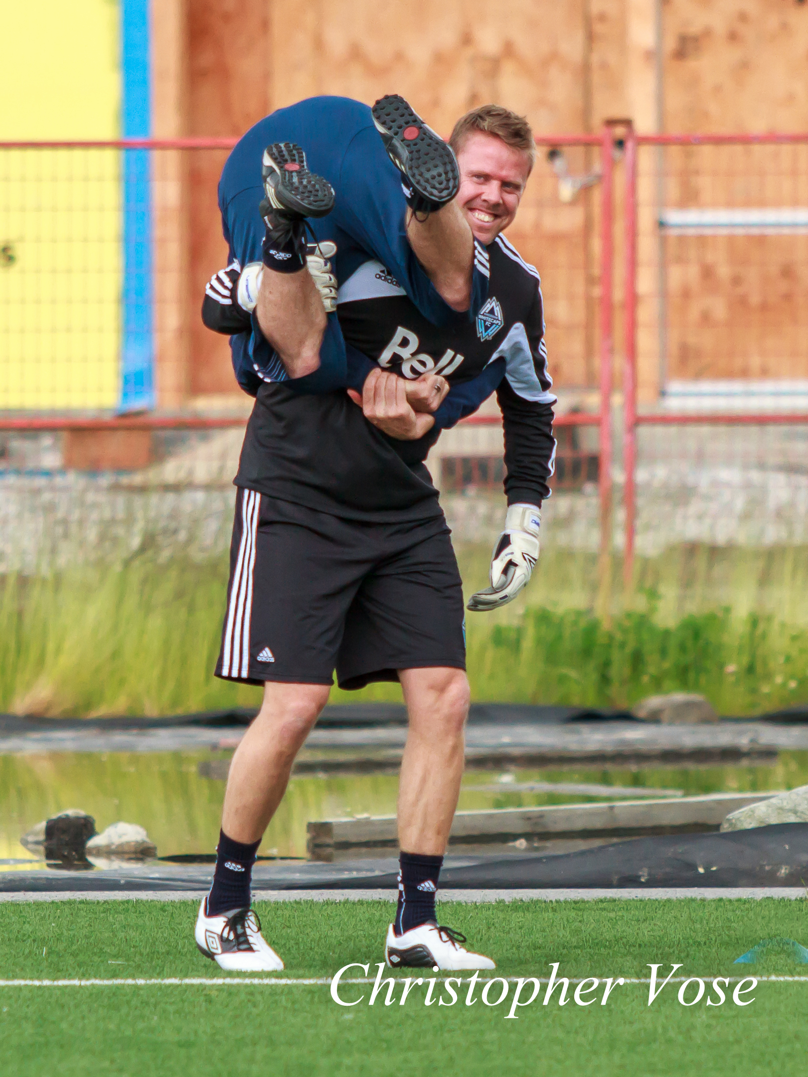 Marius Røvde prepares for his 40th birthday by carrying Vancouver Whitecaps FC physiotherapist Graeme Poole around the pitch at the Burnaby Lake Sports Complex on 14 June 2012.