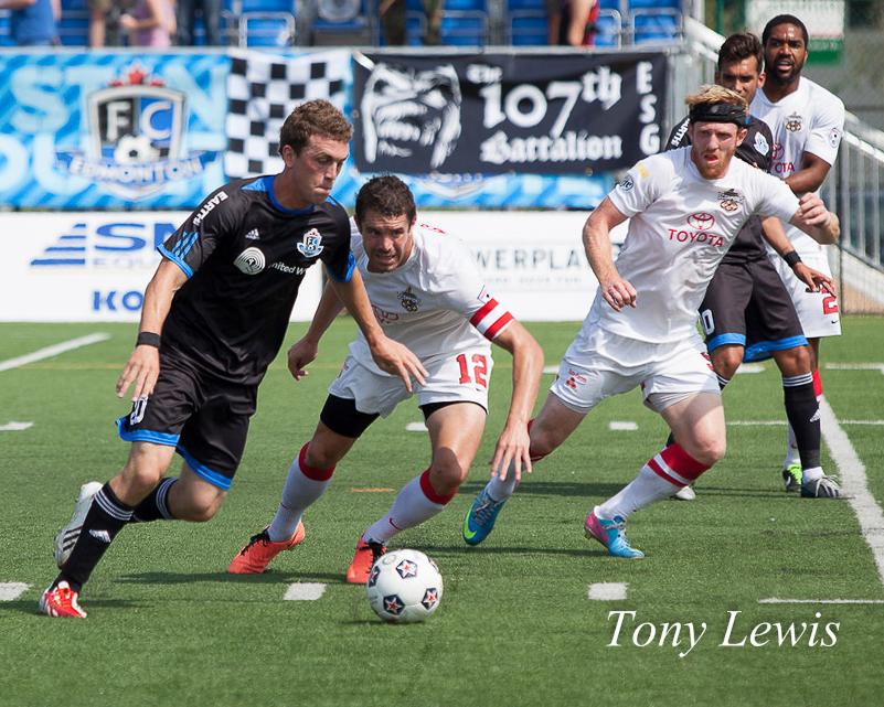 FC Edmonton's Corey Hertzog and San Antonio Scorpion FC's Greg Janicki battle for the ball at Clarke Stadium on 11 August 2013.
