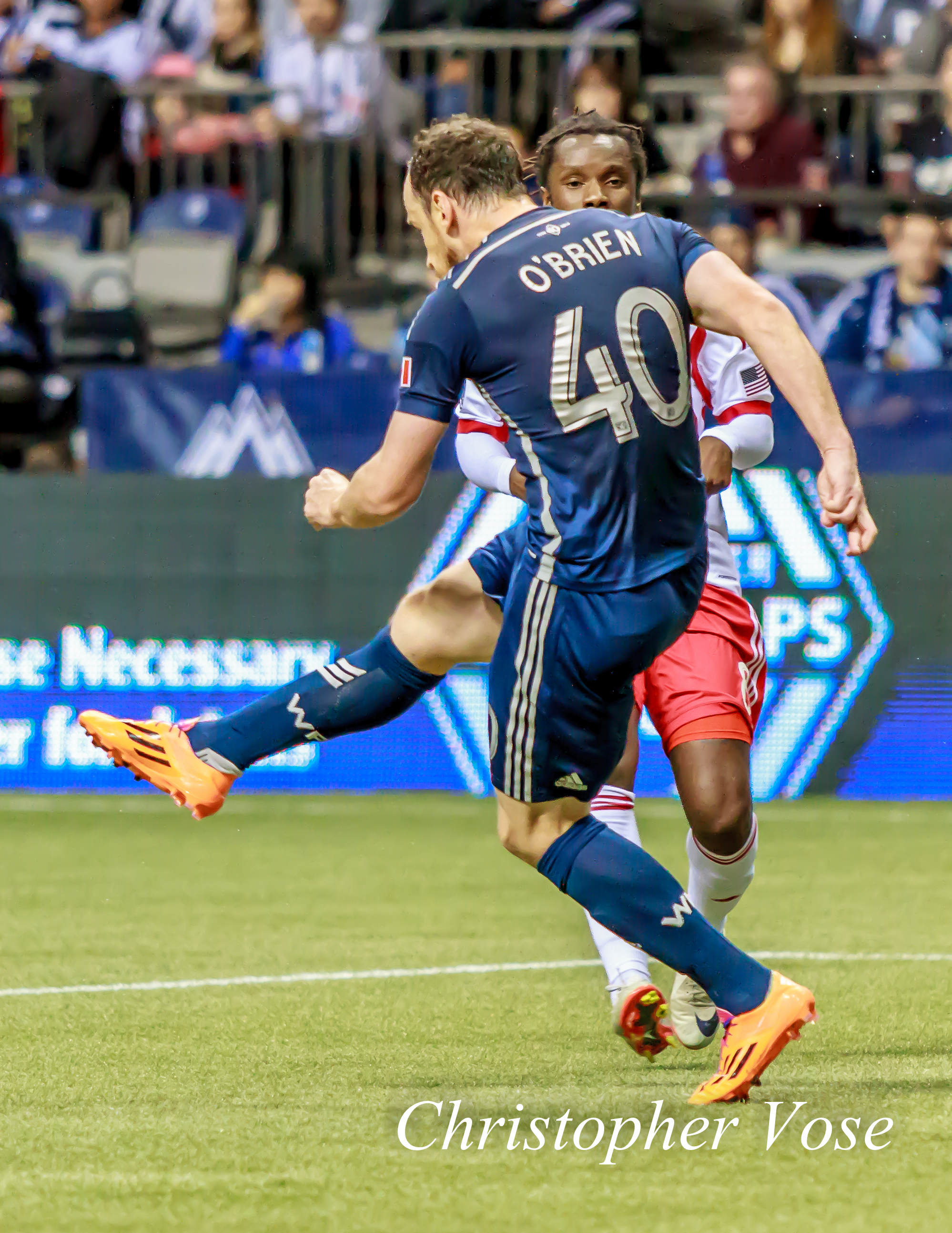 Andy O'Brien clears the ball from danger as Peguy Luyindula looks on at BC Place on 8 March 2014.