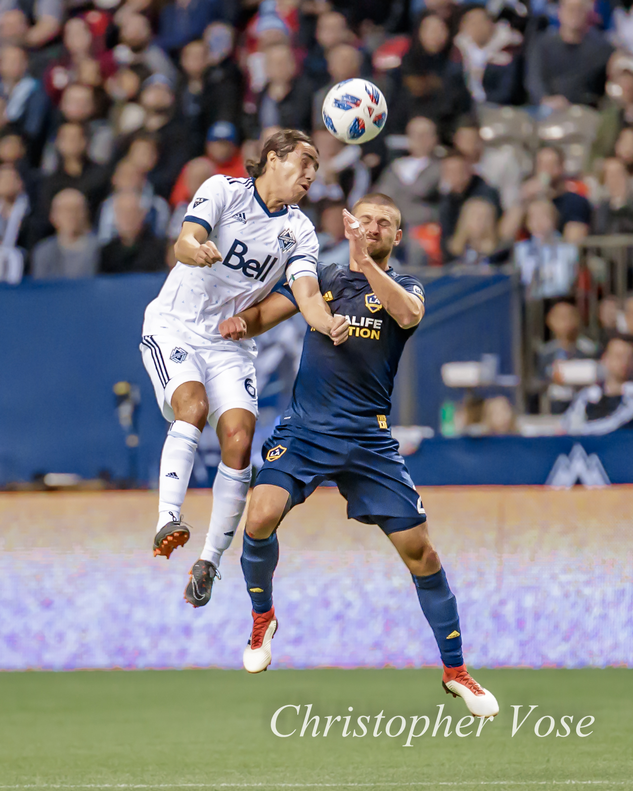 Efrain Juárez perfectly times a header over a leaping Perry Kitchen at BC Place
